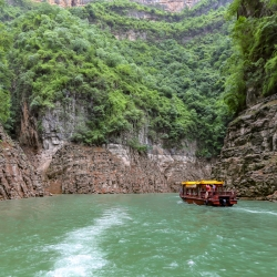 Motoring up a Yangtze tributary defined by steep cliffs above.